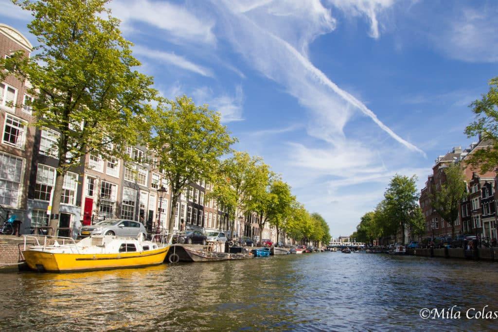 Bateaux, soleil et ciel bleu sur les canaux d'Amsterdam